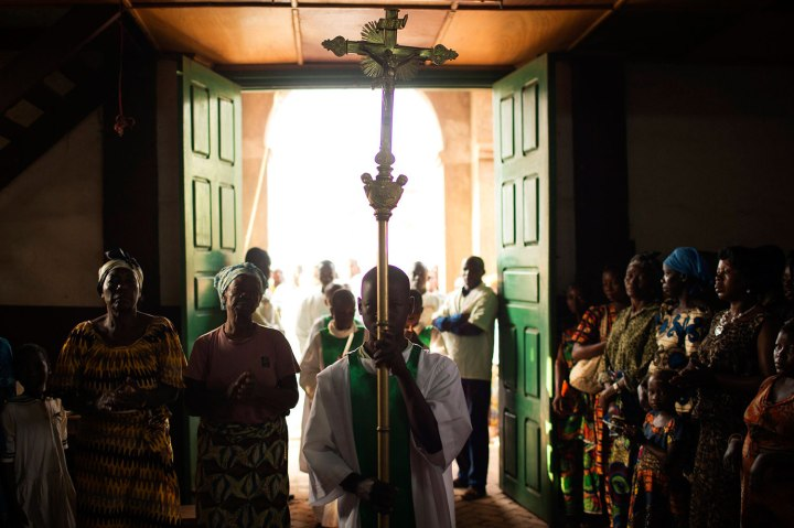 A boy carries a cross at the beginning of Sunday mass in a church in Wango