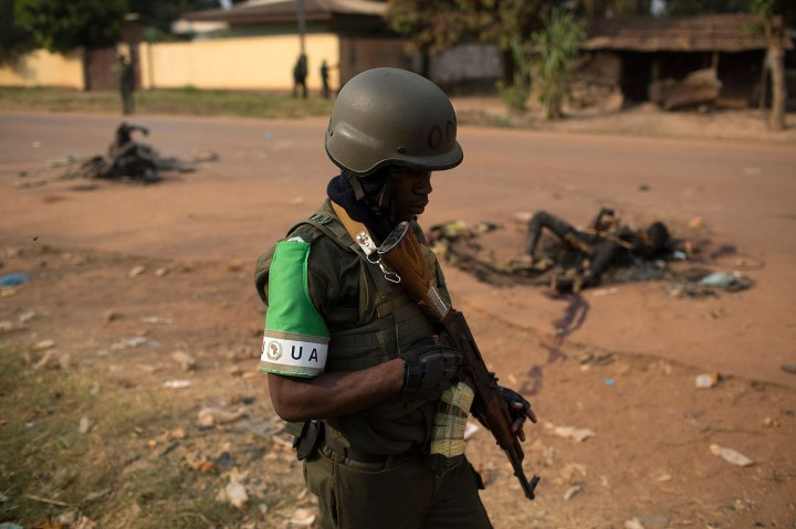 An AU peacekeeping soldier walks past burnt bodies of two Muslim men killed by a crowd in a street of the capital Bangui
