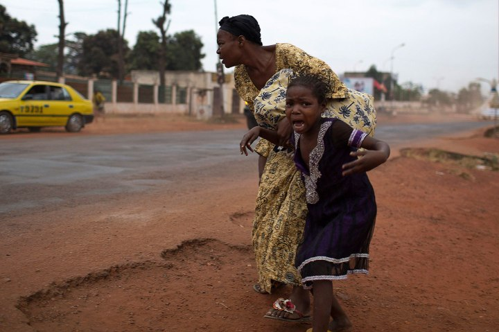 A mother holds her child while attempting to take cover as repeated gun shots are heard close to Miskine district during continuing sectarian violence in the capital Bangui