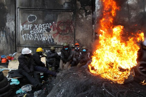 Anti-government protesters sit around a fire near barricades at the site of clashes with riot police in Kiev