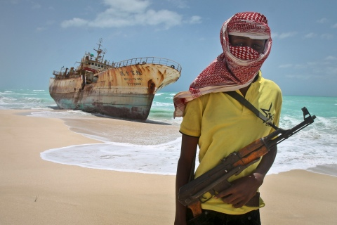 Masked Somali pirate Hassan stands near a Taiwanese fishing vessel that washed up on shore after the pirates were paid a ransom and released the crew, in the once-bustling pirate den of Hobyo, Somalia., on Sept. 23, 2012.