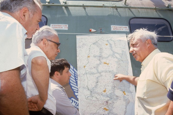 From right: Israeli Minister of Agriculture Ariel Sharon shows Minister of Justice Shmuel Tamir and U.S. Trade Ambassador Robert Strauss a map of West Bank settlements, in Israel, in July 1979.