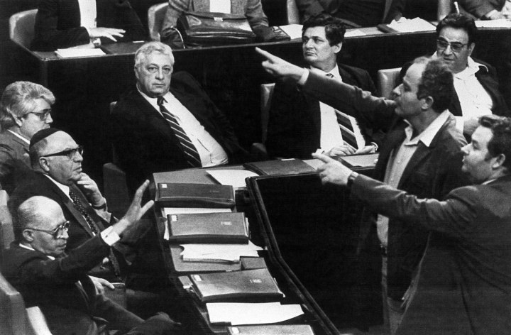 From left: Israeli Prime Minister Menahem Begin raises his hand as votes are counted on Feb. 14, 1983 as Knesset endorses removal of Ariel Sharon as Defense minister.