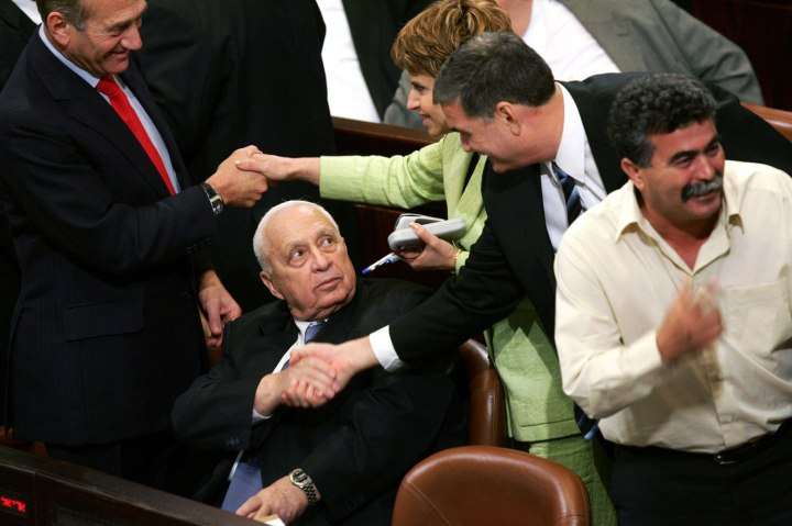 Israeli Prime Minister Ariel Sharon (center) and his Deputy Prime Minister Ehud Olmert (left) are congratulated by opposition Labor Party parliamentarians Haim Ramon and Dalia Itzik after the passing of Sharon's Gaza disengagement plan in the Knesset, at Israel's parliament in Jerusalem, on Oct. 26, 2004.