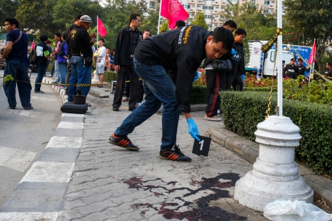 A forensic police officer drops a marker next to blood at the site of what police say was clashes between anti-government protesters and supporters of PM Yingluck Shinawatra in Bangkok