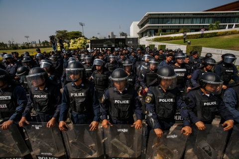 Riot police officers stand guard at the gate of the Army Club where Thailand's Prime Minister Yingluck Shinawatra is holding a cabinet meeting in Bangkok