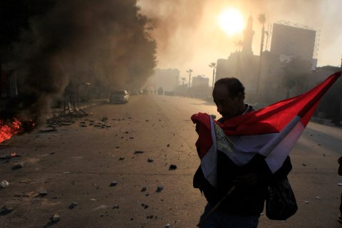 Anti-government protester holds a national flag during clashes at Ramsis street, which leads to Tahrir Square in downtown Cairo