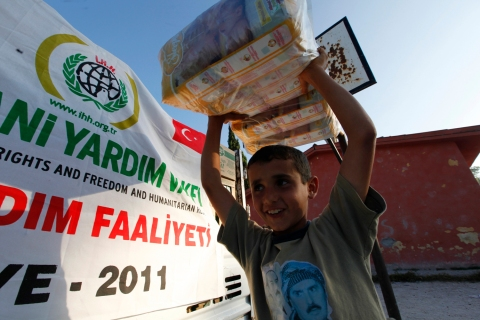 A boy assists IHH officials loading humanitarian aid for Syrian refugees into a truck in the Turkish border village of Guvecci
