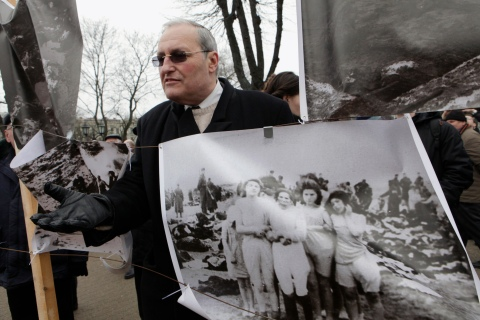 Efraim Zuroff stands beside a poster showing Nazi war crimes as he attends a protest against the annual procession commemorating Latvian Waffen SS unit, also known as the Legionnaires, in Riga, on March 16, 2012.