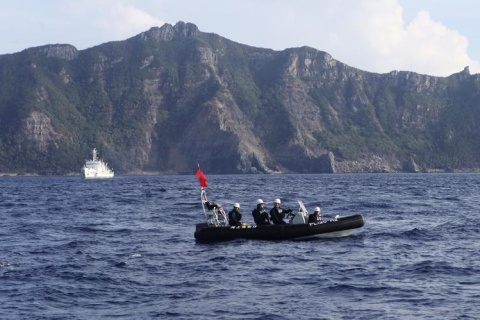 A Japan Coast Guard boat and vessel sail as one of the disputed islands is pictured in the background, in the East China Sea