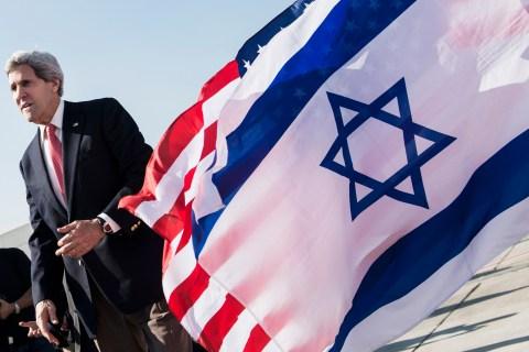 U.S. Secretary of State John Kerry walks past American and Israeli flags at Ben Gurion International Airport in Tel Aviv, on Jan. 6, 2014.