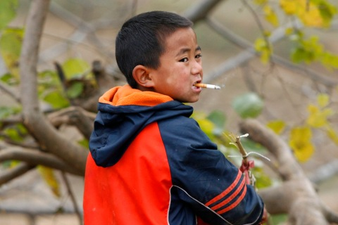 A boy smokes a cigarette as he plays with fire crackers near Zaojie in southwest China's Sichuan province