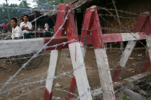 A Rohingya man looks out from a barbed wire fence used as a barrier to restrict travel on Nov. 25, 2012 on the outskirts of Sittwe, Myanmar.