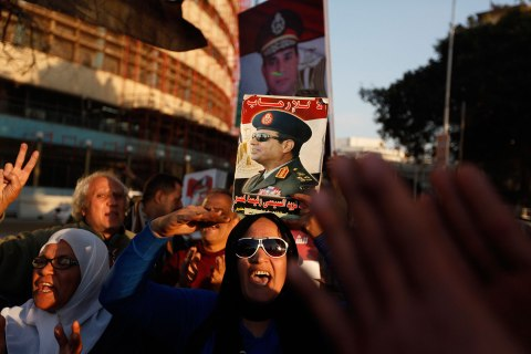 Anti-Mursi protesters hold up posters of Egypt's army chief Abdel Fattah al-Sisi during protest supporting al-Sisi in front of the state television building, central Cairo