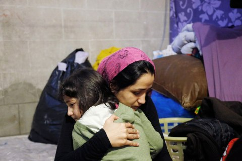 Shams consoles her daughter as they sit in a tent at the Church of Saint John the Baptist at the Beguinage in central Brussels