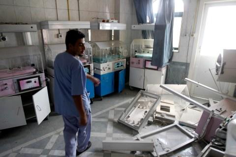 A man walks through a room at Dar Al Shifa Hospital, damaged in a Syrian Air force air strike the day before, in the Sha'aar neighbourhood of Aleppo on Aug. 15, 2012.