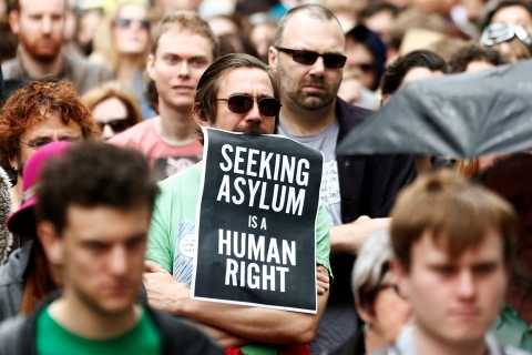 Man holds a poster during a raly in support of asylum seekers in central Sydney