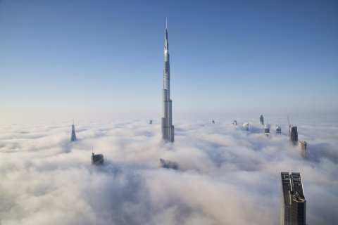 The world's tallest building pierces through a dense blanket of fog as the famous Dubai skyline is covered by fog.