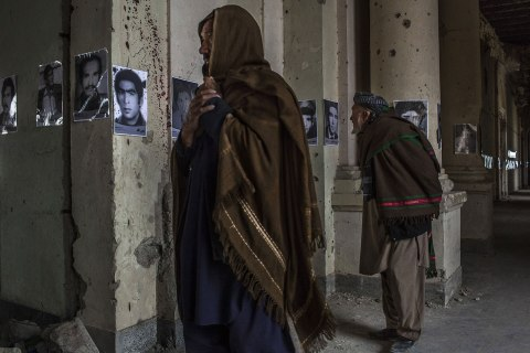 Afghan men look at photographs of people killed in the last three decades of conflict in the country at an exhibition in the ruins of the Darul Aman palace in Kabul, Afghanistan.