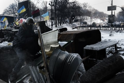 An anti-government protester sits at a road block in Kiev on Feb. 1, 2014.