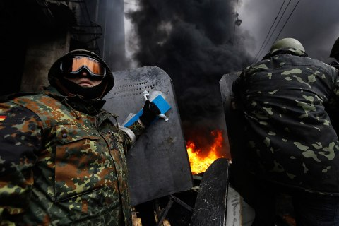 Anti-government protesters prepare to advance over a burning barricade in Kiev's Independence Square