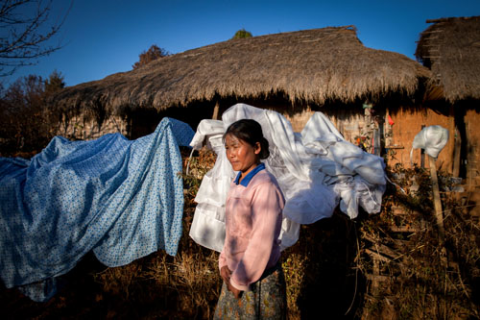 Galau Dau Yang, 35, stands outside her home in the northern Shan State village of Kut Khaing.