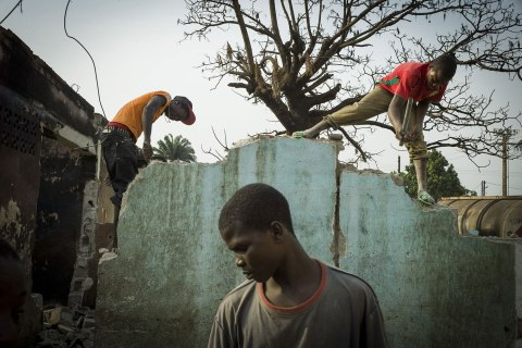 Young men take part in the destruction of houses in the PK5 neighborhood of Bangui, Central African Republic, on Feb. 17, 2014.