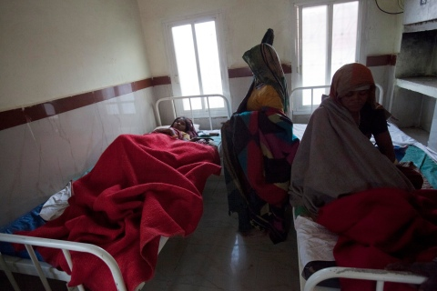 A woman who just given birth lies on a bed along with her new born baby in the post delivery ward at a community health centre Chharchh