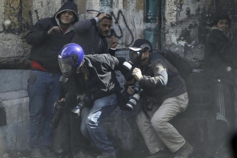 Photographers cower as protesters throw stones towards riot police in Cairo