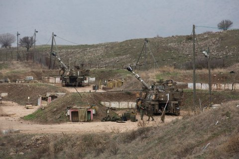 Israeli soldiers stand next to mobile artillery vehicles on the Israel-Lebanon border near Kiryat Shmona
