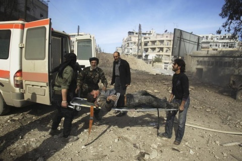 Men hold a wounded civilian