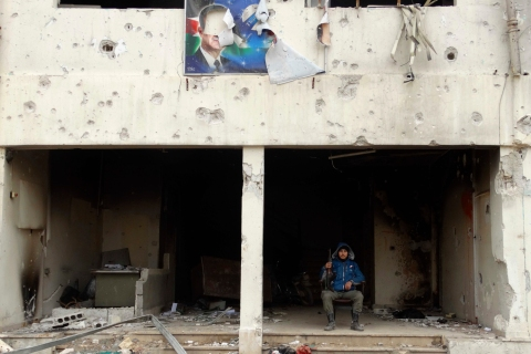 A Free Syrian Army fighter poses with his weapon under a torn picture of Hafez al-Assad, father of President Bashar Al-Assad, at the Tameko pharmaceutical factory, in eastern al-Ghouta