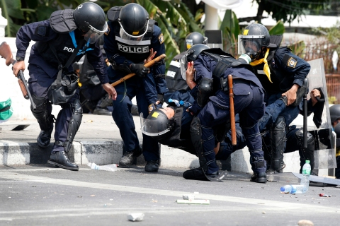 Thai police officers assist a colleague after an explosion during clashes with anti-government protesters near Government House in Bangkok