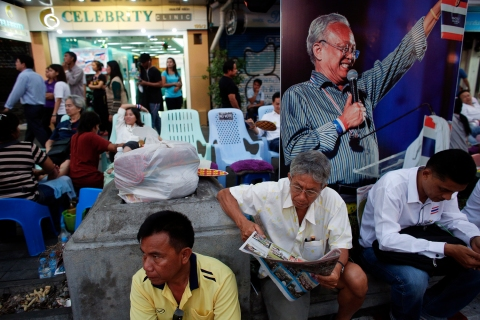 Anti-government protesters enjoy a massage and read papers near a picture of protest leader Suthep Thaugsuban in an occupied area, in downtown Bangkok