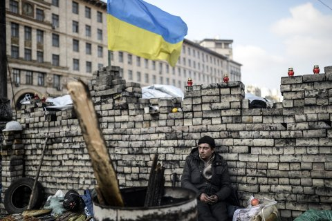 An anti-government protester sits behind a barricade on Kiev's Independence Square on February 24, 2014.