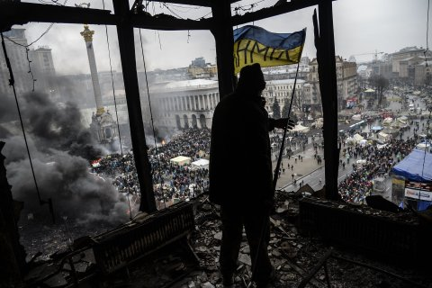 A demonstrator stands on a balcony overlooking Independence square in Kiev, February 20, 2014.