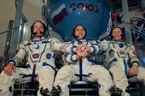 NASA astronaut Steven Swanson joins hands with Russian cosmonauts, Alexander Skvortsov and Oleg Artemyev in front of a mock-up of a Soyuz TMA spacecraft at the Gagarin Cosmonauts' Training Centre in Star City centre outside Moscow, on March 5, 2014.