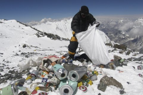 A Nepalese sherpa collects garbage left by climbers at an altitude of 8,000 metres during the Everest clean-up expedition at Mount Everest, on May 23, 2010.