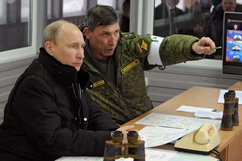 Russia's President Vladimir Putin (L), and head of the Russian army's main department of combat preparation Ivan Buvaltsev watch military exercises at the Kirillovsky firing ground in the Leningrad region, March 3, 2014.